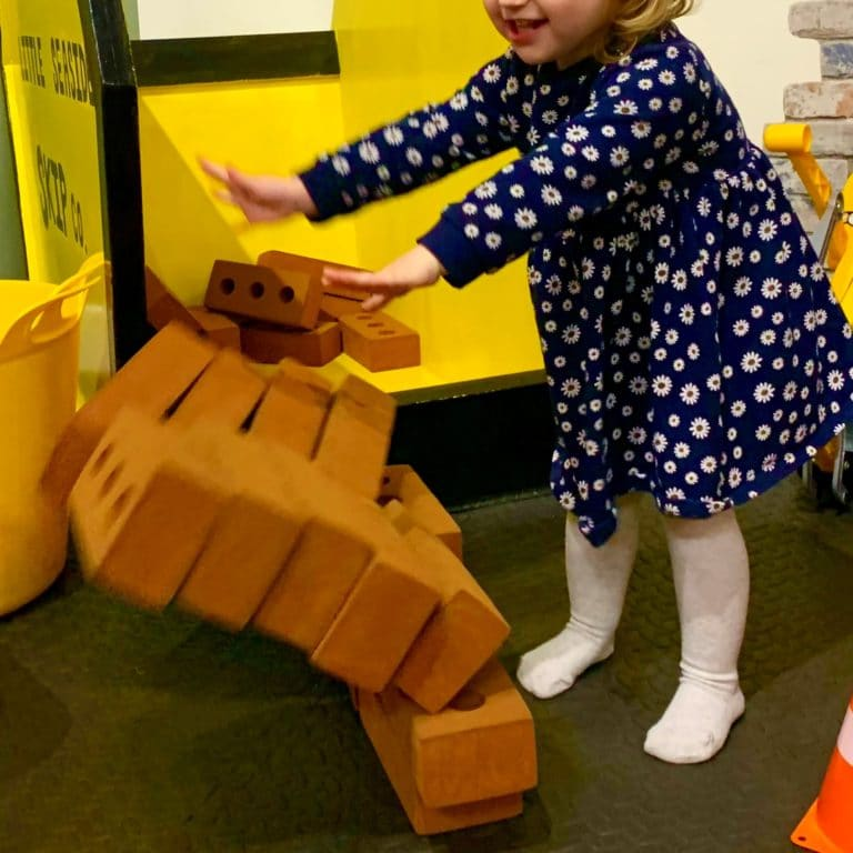 A toddler pushing over a wall of toy bricks